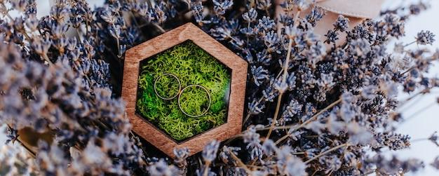 Два обручальных кольца в деревянной коробке с моховым растением на фиолетовых цветках лаванды