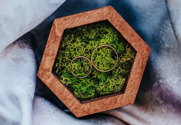 Два обручальных кольца в деревянной шкатулке с растительным мохом на фиолетовой ткани