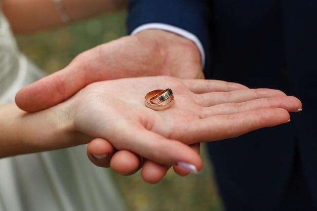 新婚夫婦の手にある2つの結婚指輪がクローズアップ。結婚式。結婚式の日