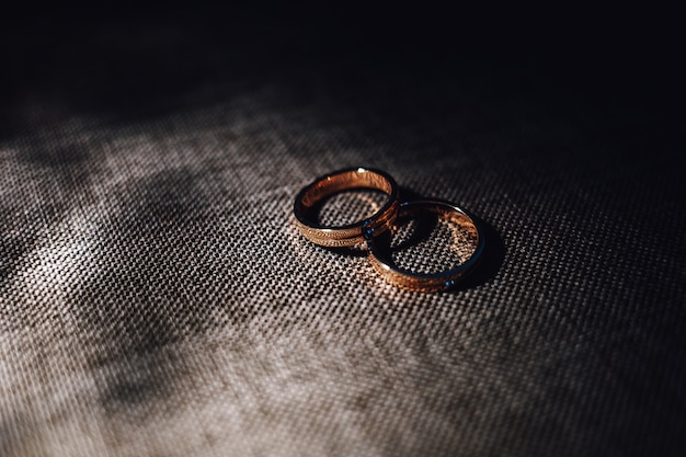 Two wedding rings lie on a gray fabric