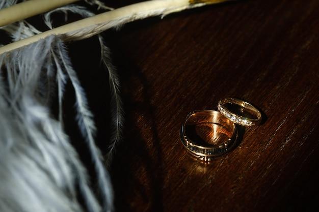 두 개의 결혼 반지는 흰색 깃털에 놓여 있습니다. 사랑의 개념입니다.