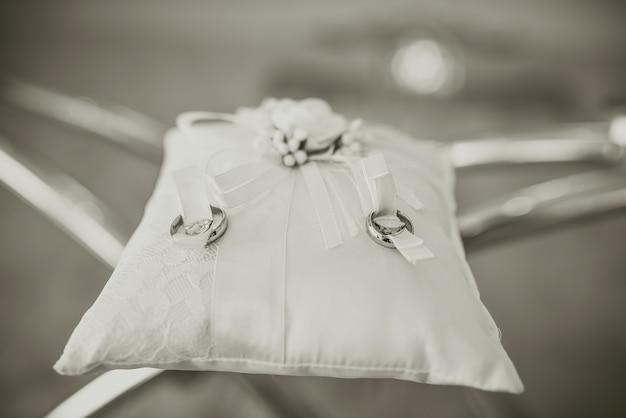 2つの結婚指輪は、透明なガラスのテーブルの刺繍されたシルクのクッションの上にあります