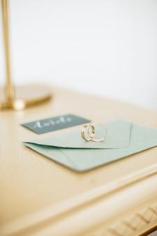 Два обручальных кольца лежат на приглашении с золотым фоном