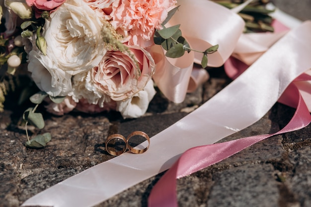 Two wedding rings lie on a tape of a wedding bouquet