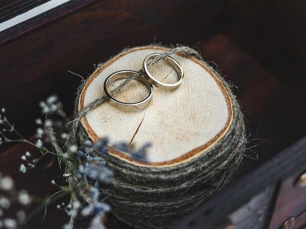Два обручальных кольца, лежащих на фоне цветов