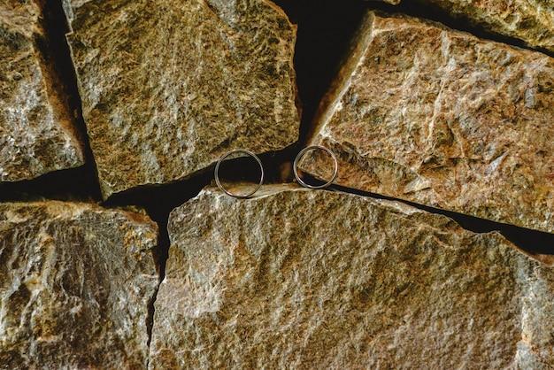 二人の愛情のある連合を象徴する岩の上の2つの結婚指輪。