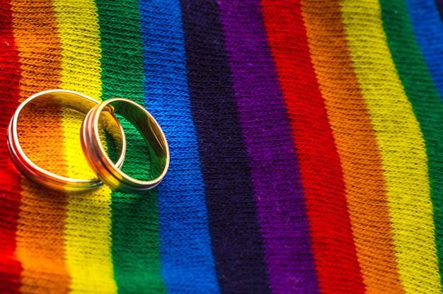 虹の生地の色に2つの結婚指輪。同性結婚の概念。対処スペース