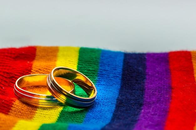 虹の生地の色に2つの結婚指輪。同性結婚の概念。