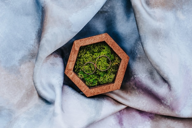 Two wedding rings in a wooden box with a plant moss on a purple fabric surface