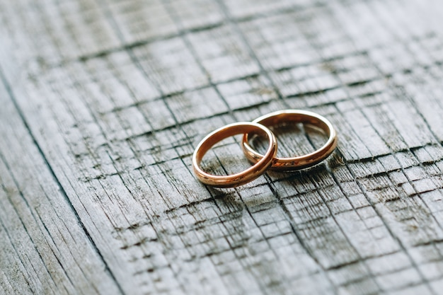 Two wedding rings on a wooden texture