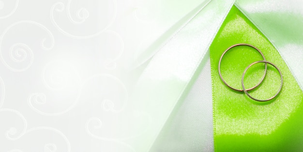Two weddings rings on the fabric background