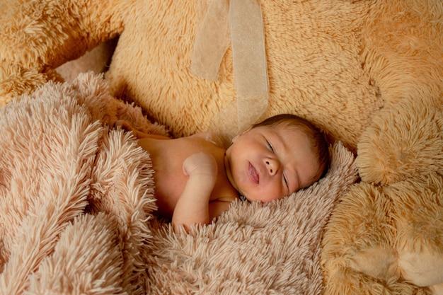 Двухнедельный новорожденный ребенок спит на плюшевом мишке
