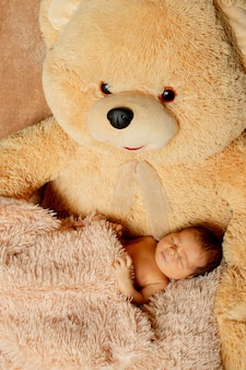 Two week old newborn baby sleeping on teddy bear