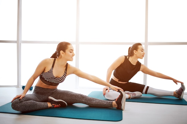 Two well-built young women stretch legs together in fitness room. each of them reach foot with one hand. they exercise in front of window