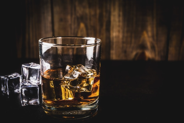 Two whiskey shot glasses on dark wooden table, with ice cubes,