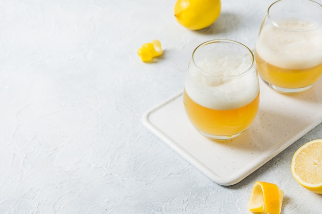 Два виски кислые коктейли с ингредиентами, лимонный сок, сахарный сироп и яичный белок в стакан на белом. горизонтальная ориентация.
