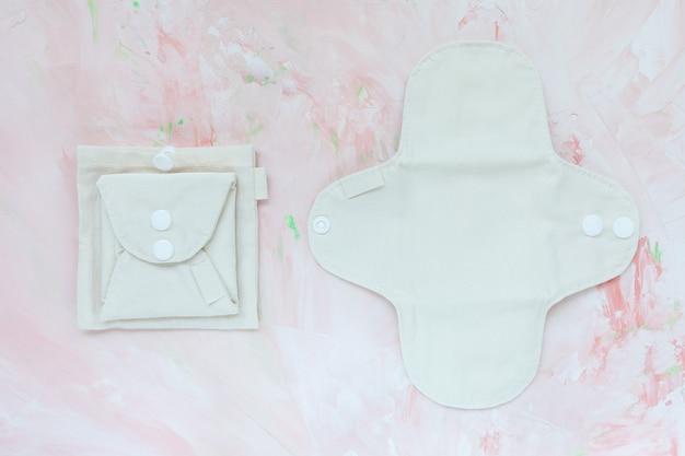 2つの白とベージュの洗える健康的な再利用可能な生理用パッド、生理用綿、折りたたみ、バッグ付き、コピースペース。フェミニンな抗アレルギー衛生、環境にやさしい、プラスチックを含まない、無駄のないライフスタイルコンセプト