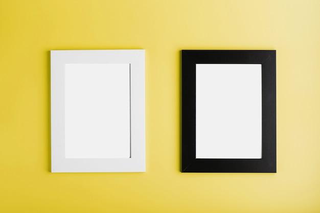 노란색 표면에 두 개의 흰색과 검은 색 사진 프레임