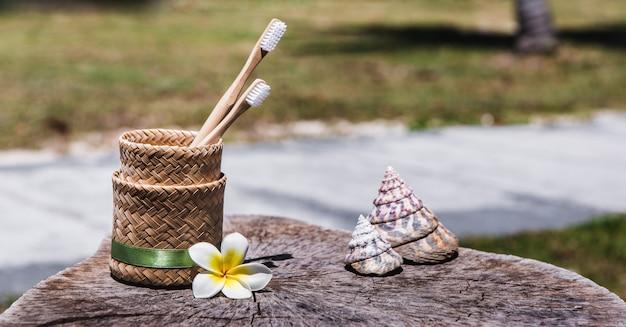 Две белые и желтые экологически чистые бамбуковые деревянные зубные щетки в держателе на деревянном