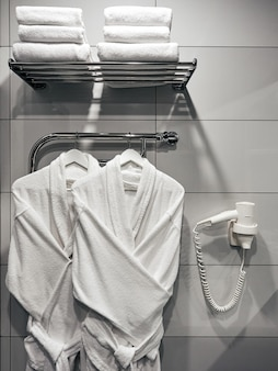 Two white bathrobes in the bathroom on the wall with a white hairdryer and towels in the hotel