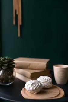두 개의 흰색 아름 다운 맛있는 마쉬 멜 로우는 테이블에 커피와 책 한 잔 옆 테이블에 놓여 있습니다. 고품질 사진