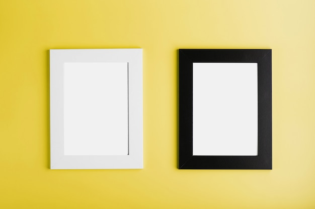 Two white and black photo frames on yellow surface