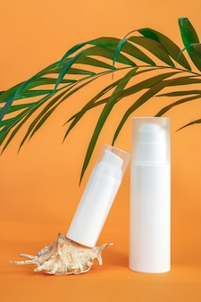 Two white blank cosmetics bottles with sunscreen, suncream or other cosmetic product, seashell and palm