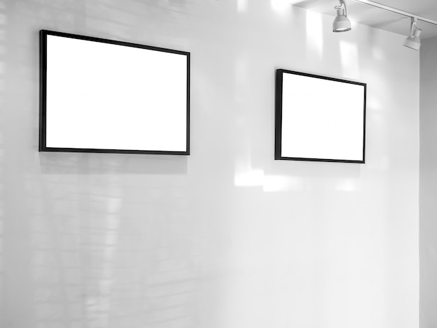 Two white blank frames on white wall background