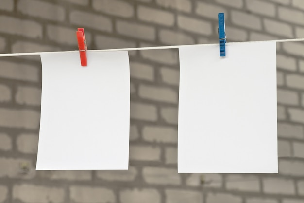 Two white blank sheets of notes with clothespins hanging