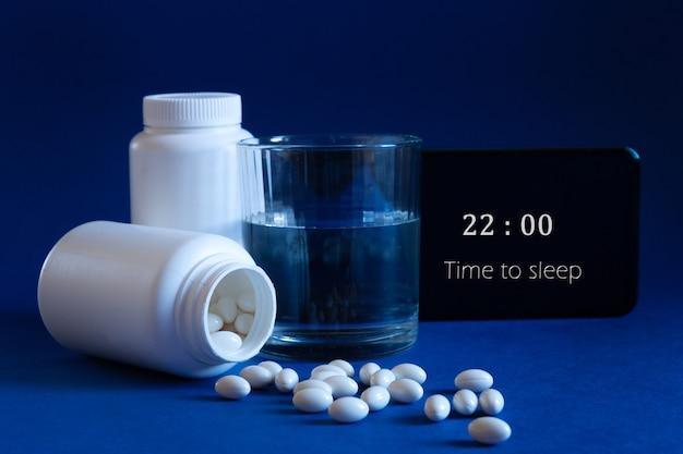 Две белые бутылки, таблетки и экран мобильного телефона с часами на синем фоне. понятие бессонница, время полнолуния, проблемы со сном, снотворное. мокап, копировать пространство