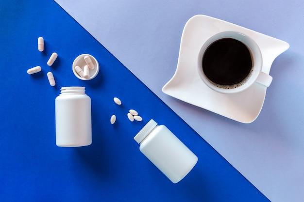 Две белые бутылки, таблетки, кофейная чашка на синем фоне. понятие бессонница, время полнолуния, проблемы со сном, снотворное. макет, вид сверху, плоская планировка, копия пространства.