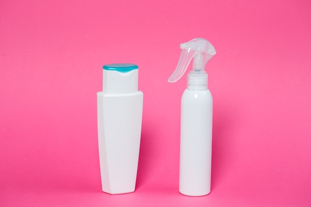 Two white bottles with shampoo for hair, body gel, spray for the skin on a pink background