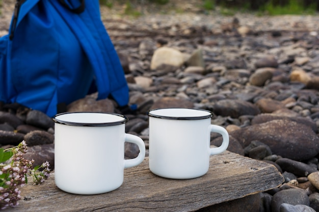 Two white campfire mug mockup with blue backpack