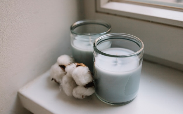 Two white candle jars with cotton pod