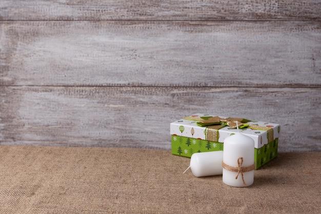 Две белые свечи в джутовой веревке и зеленая подарочная коробка