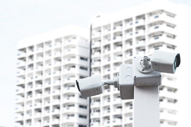 Две белые камеры видеонаблюдения наблюдают за принадлежащим имуществом и зданием имени охранника.
