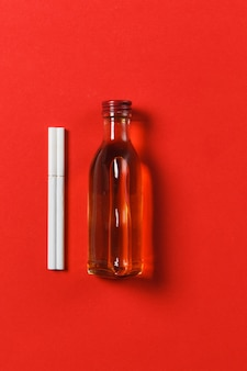 Two white cigarettes, bottle with alcohol cognac, whiskey on red background