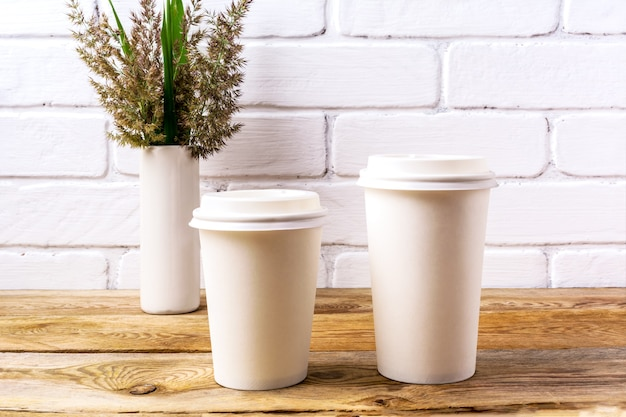 Two white coffee disposable hot paper cup with lid mockup with cordgrass and green leaves