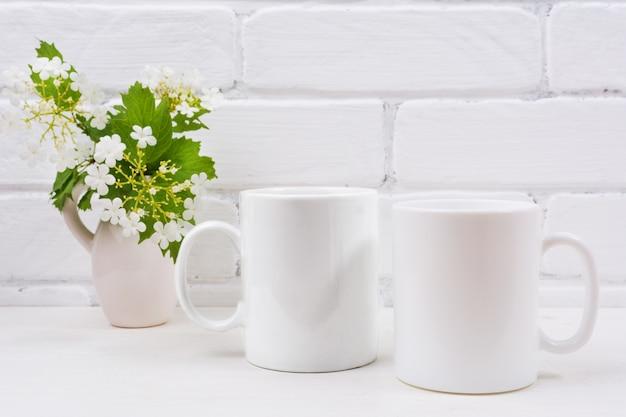 ガマズミ属の木の花を持つ2つの白いコーヒーマグモックアップ