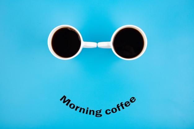 モーニングコーヒーというフレーズで青い背景に笑顔で2つの白いコーヒーマグ。