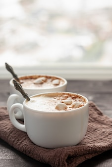 Two white cups of cappuccino across the window with spoons inside cups. close up photo with selective focus
