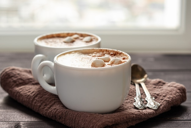 Two white cups of cappuccino with marshmallows and spoons on wooden table. close up photo with selective focus