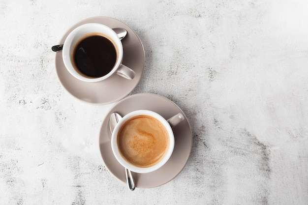 Two white cups of hot black coffee with milk isolated on bright marble background. overhead view, copy space. advertising for cafe menu. coffee shop menu. horizontal photo.