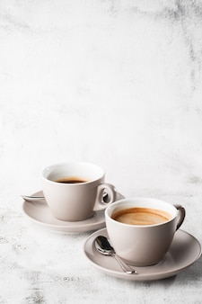 Two white cups of hot black coffee with milk isolated on bright marble background. overhead view, copy space. advertising for cafe menu. coffee shop menu. vertical photo.