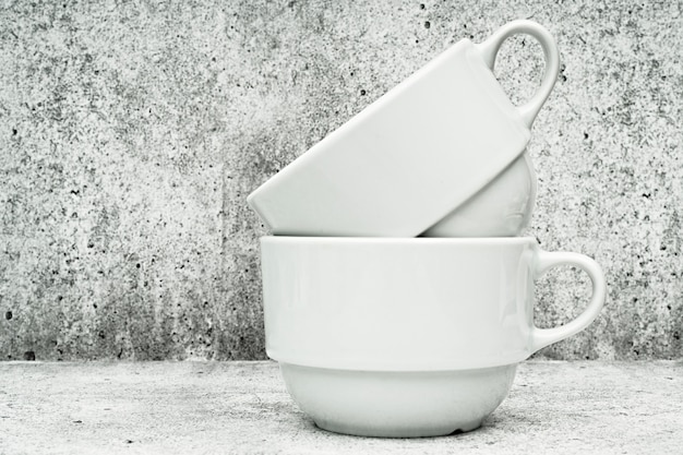 Two white cups on a light background