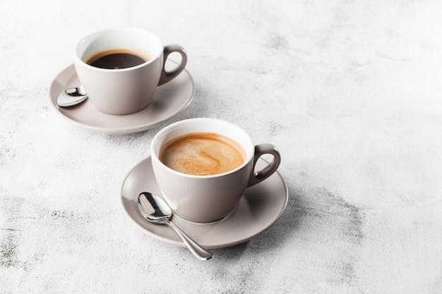 明るい大理石の背景に分離したミルクとホットブラックコーヒーの2つの白いカップ。俯瞰、コピースペース。カフェメニューの宣伝。コーヒーショップメニュー。横の写真。