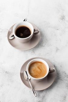 明るい大理石の背景に分離されたミルクとホットブラックコーヒーの2つの白いカップ