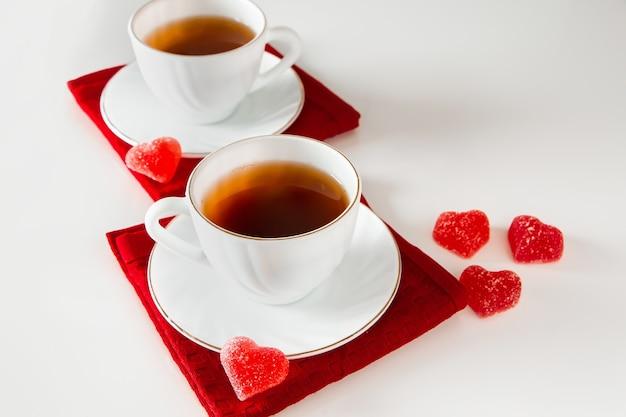 Две белые чашки чая на белом фоне. мармелад в форме сердца, символ дня святого валентина и любви. концепция встречи двух влюбленных.