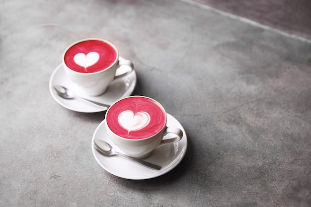 Two white cups of trendy corolful beetroot latte with love art latte.