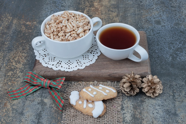 Due tazze bianche con biscotti di natale e due pigne su tavola di legno.